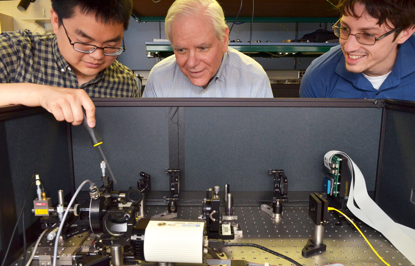 From left to right, PhD candidate Joseph Tang, Prof. James Fienup, and PhD candidate Scott Paine in the lab where they use a MEMS  (microelectromechanical system) deformable mirror to simulate the James Webb Space Telescope and test the phase retrieval algorithms the lab has developed to realign the telescope's 18 mirrors.