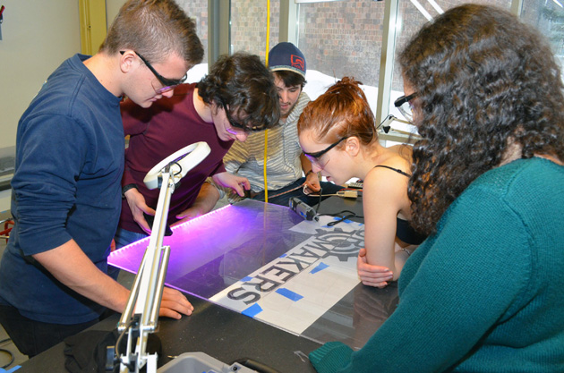 Group of students working on a sign.