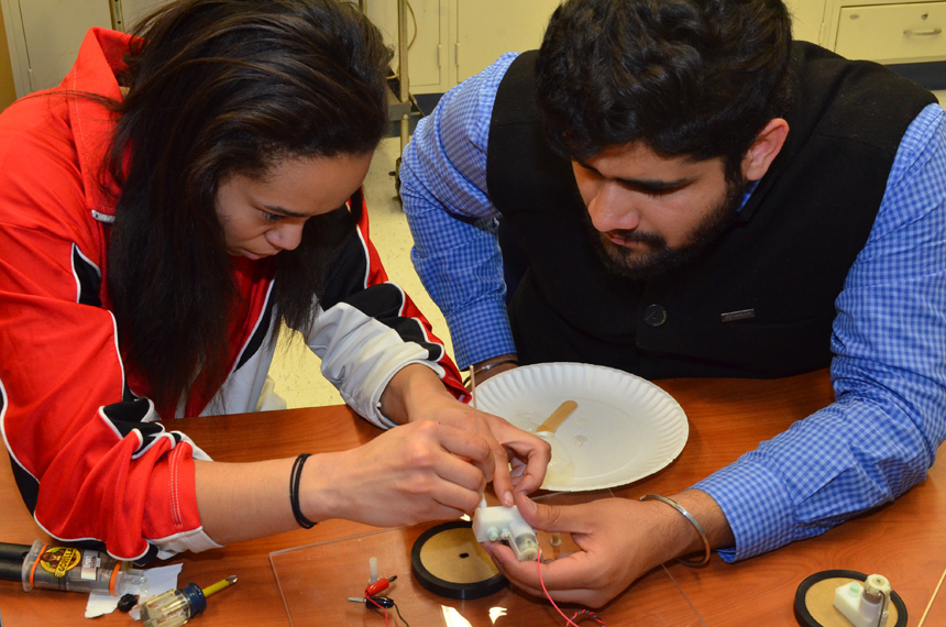Londrea Garrett and Ekam Singh Gill help assemble wheels for the Chem-E-Car.