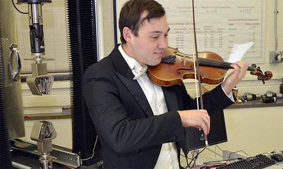 Ivan Suminski plays violin in a mechanical engineering lab while Prof. Chris Muir records the sounds for later analysis.