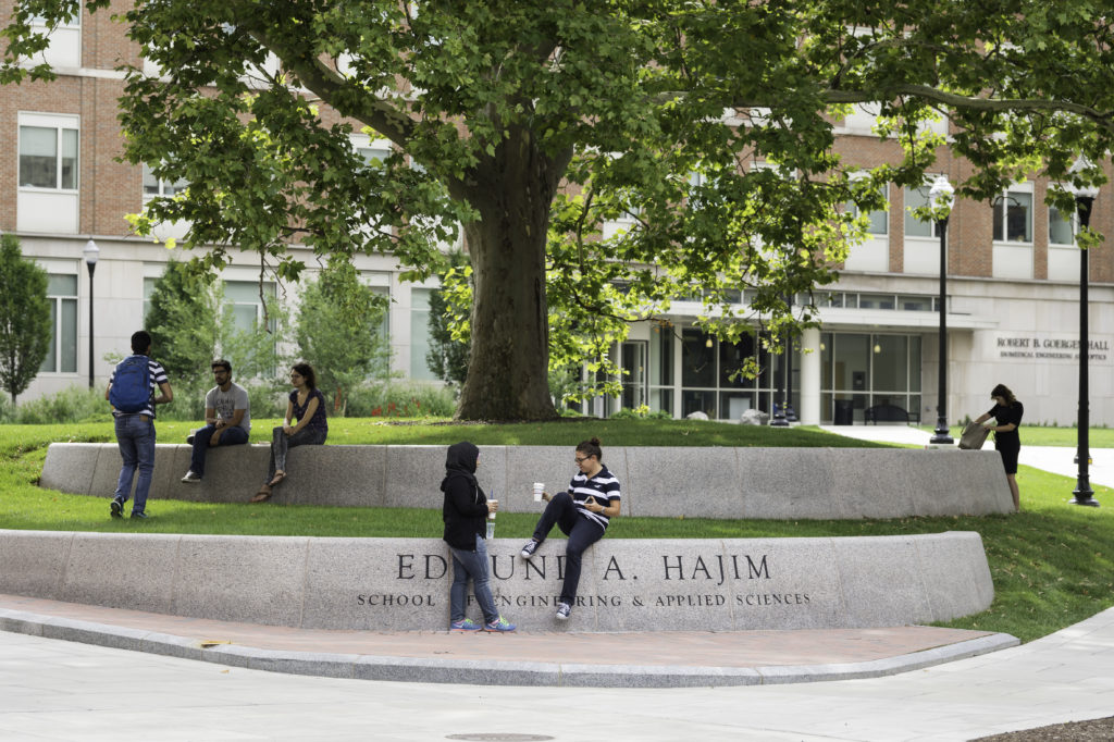 Five students sit and stand in groups on concrete steps underneath a large tree with many leaves on it. On the lower cement step is engraved Edmund A Hajim School of Engineering & Applied Sciences.